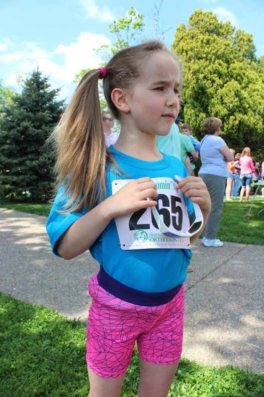 Olive and her first official race bib. Ever the fashionista you will note the requested side ponytail.